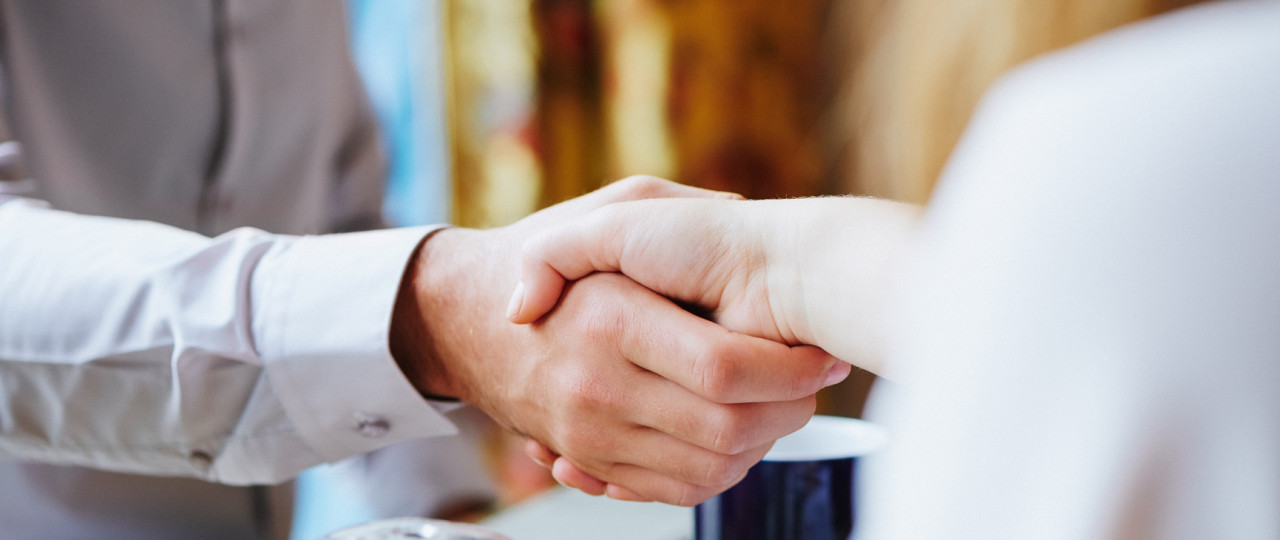 Business agreement being made with a handshake in a cafe