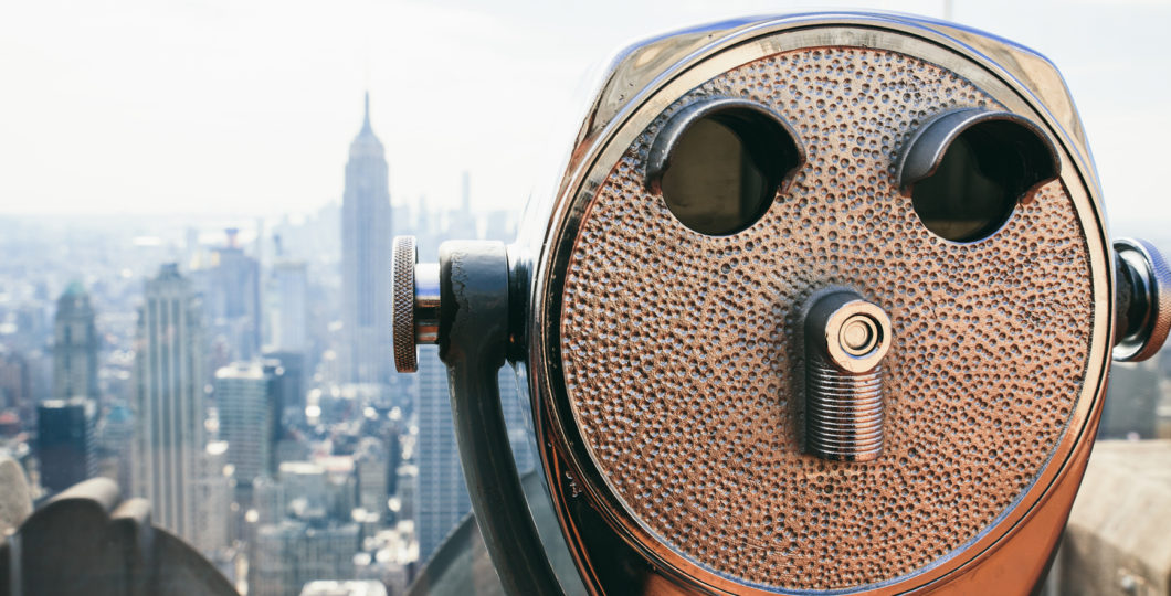 New York cityscape in sunlight with binoculars on foreground