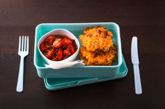 Stack of potato fritters and a bowl of cherry tomato salad in a lunch box on a wooden table