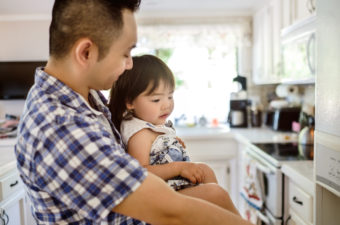 A shot of a little Asian girl with her dad in the kitchen